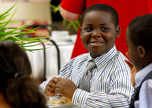 Kendrick Peyton, a third-grader at Mount Tabor Elementary School, talks with friends during the school's seventh annual tea party. Students learned about proper table manners and how to act in formal social settings. Staff photo by Jerod Clapp