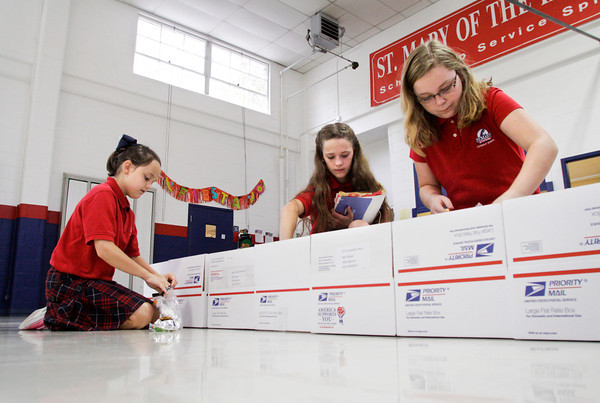 From left, St. Mary of the Knobs fifth-graders Chloe Sprigler, Regan Elias and Brigid Welch work on care packages for 12 Indiana National guardsmen deployed in Afghanistan in the school gymnasium on Friday morning. One of the guardsmen is Capt. Adam Paris, the son of their teacher, Kimberly Paris, and they are sending the care packages as well as a banner to mark the halfway point of his year-long deployment. Staff photo by Christopher Fryer