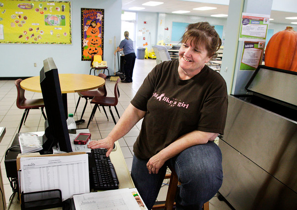 "Assistant cafeteria manager Jody Robert, of Georgetown, wears a ""fight like a girl"" breast cancer awareness shirt while ringing up students at Georgetown Elementary School. Robert crochets items and sells them online with a percentage of the profits going to the American Cancer Society's Making Strides Against Breast Cancer. Staff photo by Christopher Fryer"