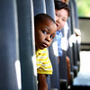 Terrence Brackens looks up the aisle as he and other incoming kindergarten students take a bus ride as part of Camp Kindergarten at Bridgepoint Elementary School on Thursday evening. Staff photo by C.E. Branham