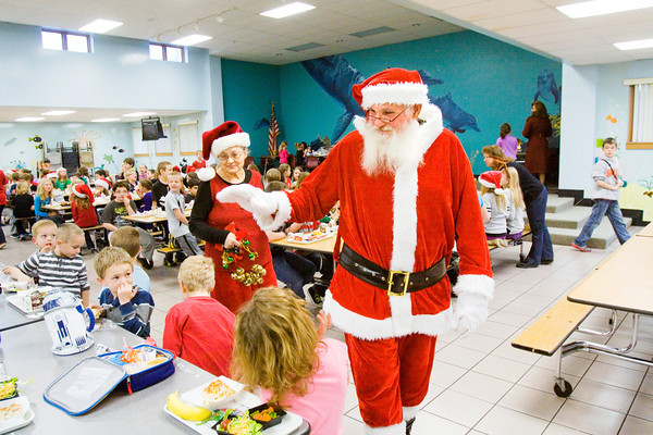 Georgetown residents Steve and Carol Weaver visit with Georgetown Elementary School students while dressed as Santa Claus and Mrs. Claus during a visit to the school organized by the the Georgetown Police Department on Friday morning. Staff photo by Christopher Fryer