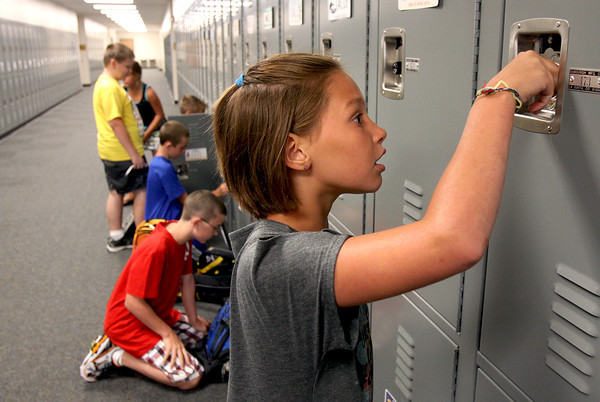 Henryville Elementary School fifth-grader Olivia Guernsey practices getting into her new locker Tuesday morning. The Henryville schools are open for business after being heavily damaged five months ago by tornadoes. Staff photo by C.E. Branham