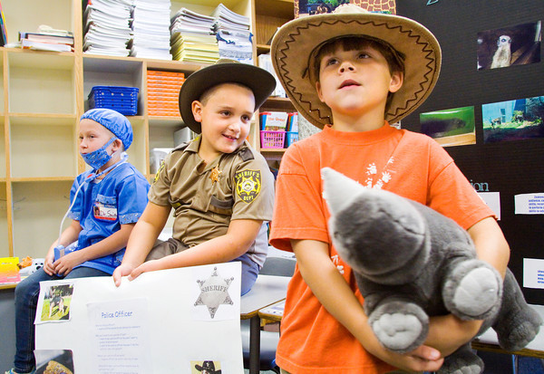 From left, second-graders Addison Smith, 7, dressed as a veterinarian, Nathan White, 7, dressed as a police officer, and Emerson Lowe, 8, dressed as a zoo keeper, stand with their displays as other students, teachers and parents attend a job fair in the second-grade classrooms of the school on Friday morning. Each second-grader chose a career they were interested in to research and dress up as for the district's College Go Week! Staff photo by Christopher Fryer