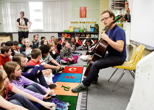 Cellist Ben Sollee plays for Slate Run Elementary fourth-graders during his workshop, On Playing A Wooden Box, at the school in New Albany on Friday morning. Sollee holds workshops at public schools in between tour dates to break the conventional wisdoms associated with the cello and demonstrate the instrument's potential outside of classical music. Staff photo by Christopher Fryer