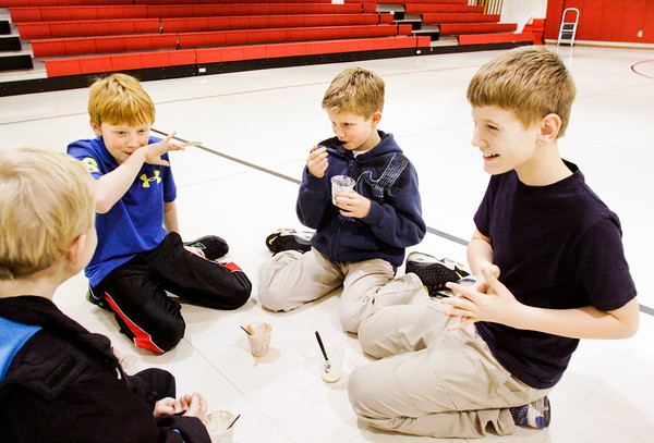 From left, St. Paul Catholic School fourth-graders Allen Kruer, 9, Jacob Braswell, 9, Sean Bowles, 9, and Aidan Mabe, 10, share a laugh as they eat ice cream during Sundaes for Sundays in their gymnasium on Wednesday afternoon in Sellersburg. The frozen treats were served up as part of the school's celebration of Catholic Schools Week. Staff photo by Christopher Fryer