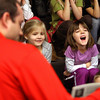 Utica Elementary School first-grader Lana Probus enjoys a story read by Jeffersonville High School girls' basketball head coach Matt Pait Wednesday afternoon. Pait and his team read to students for 100 minutes to commemorate the 100th day of school. Staff photo by C.E. Branham