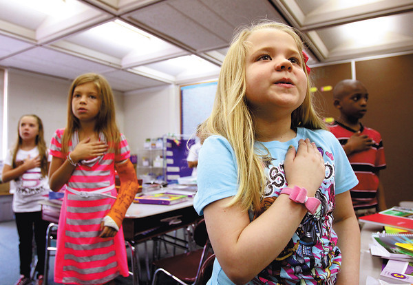 Northaven Elementary School third-grader Alexis Cook and classmates say the Pledge of Allegiance to start the school day Wednesday morning. Greater Clark County Schools welcomed back more than 10,000 students yesterday. Staff photo by C.E. Branham
