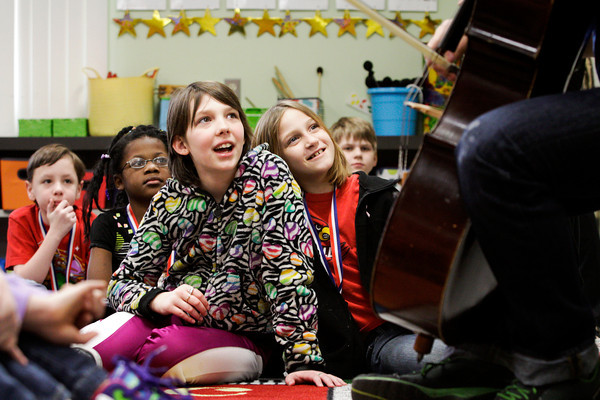 Slate Run Elementary School fourth-graders Destiny Garrett, left, and Destiny Hardy listen to cellist Ben Sollee during his workshop, On Playing A Wooden Box, at the school in New Albany on Friday morning. Sollee holds workshops at public schools in between tour dates to break the conventional wisdoms associated with the cello and demonstrate the instrument's potential outside of classical music. Staff photo by Christopher Fryer