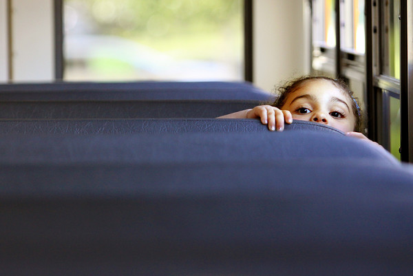 Braelyn Terry peeks over the seat as she and other incoming kindergarten students get ready to take a bus ride as part of Camp Kindergarten at Bridgepoint Elementary School on Thursday evening. Staff photo by C.E. Branham