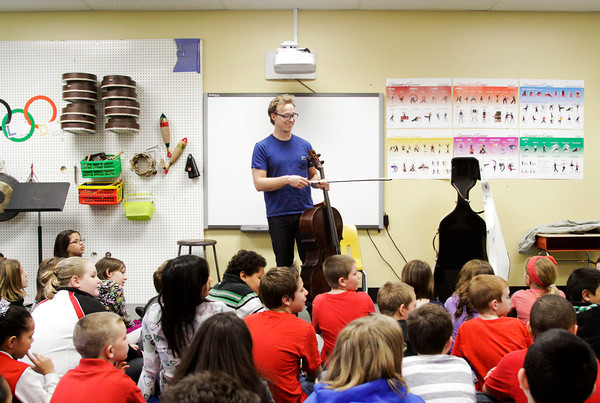 Cellist Ben Sollee speaks to Slate Run Elementary fourth-graders during his workshop, On Playing a Wooden Box, at the school in New Albany on Friday morning. Sollee holds workshops at public schools in between tour dates to break the conventional wisdoms associated with the cello and demonstrate the instruments potential outside of classical music. Staff photo by Christopher Fryer
