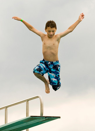 Parkwood Elementary School fourth-grader Christian Calderon leaps off a diving board at the Jeffersonville Aquatic Center on Thursday morning. Calderon and the rest of the student body from the school were rewarded with a day at the center for clocking the most steps, using pedometers, in the Greater Clark County Schools Fitness Challenge. This is the third year in a row that Parkwood has placed first in the challenge, although this year they tied with Bridgepoint Elementary School. Staff photo by Christopher Fryer