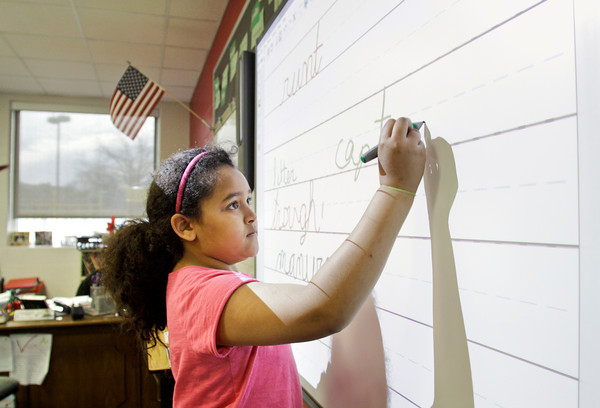 Clarksville Elementary School third-grader Issy Planche, 9, writes on a SMART Board during cursive writing exercises in her class on Thursday morning. Staff photo by Christopher Fryer