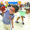 Thomas Jefferson Elementary School kindergarten student M.A.C. Carter and dozens of other students do a Jazzercise workout Thursday afternoon at the school. The program was part of the Greater Clark County Schools Mileage Club health initiative. Staff photo by C.E. Branham