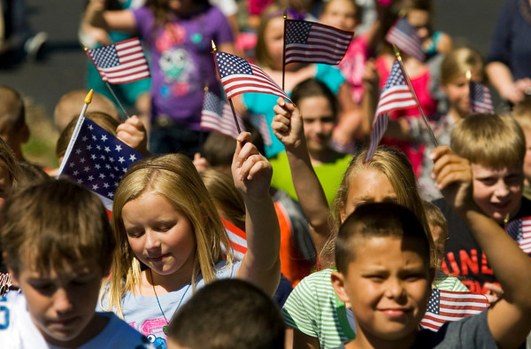 Henryville Elementary School students wave American flags as they walk around their school during the America Supports You Freedom Walk on Tuesday morning. Elementary students from each grade participated in the walk during their recess times in honor of the rescuers that responded on September 11, 2001, as well as past and present veterans. Staff photo by Christopher Fryer