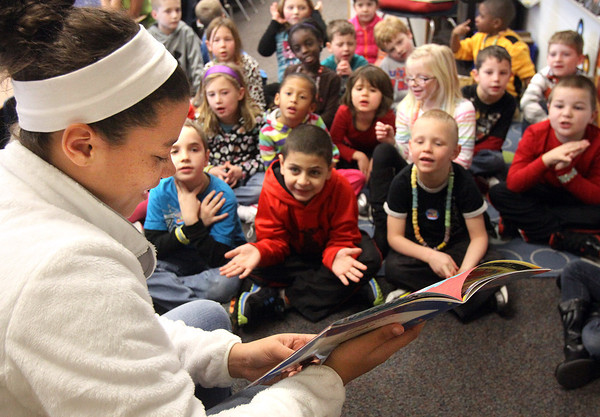 Members of the Jeffersonville High School girls' basketball team helped first graders at Utica Elementary School celebrate the 100th day of school by reading 100 minutes to the students Wednesday afternoon. Makenzi Johnson, above, reads to a group of students. Staff photo by C.E. Branham