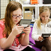Highland Hills Middle School fifth-graders Allese Veteto, left, and Amy Standiford use Amazon Kindle e-readers during their remedial reading class on Tuesday morning. The class, taught by Carla Thomas, currently has seven of the devices and will soon be acquiring three Kindle Fires to help students with mobility issues. Staff photo by Christopher Fryer