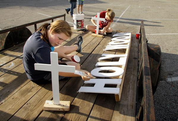 St. Mary's Catholic Academy eighth grade student council representatives Courtney Koch, left, and Elizabeth Scharre paint crosses while working on their school's Harvest Homecoming parade float on Wednesday afternoon in New Albany. The Harvest Homecoming parade will start at New Albany High School at noon on Saturday. Staff photo by Christopher Fryer