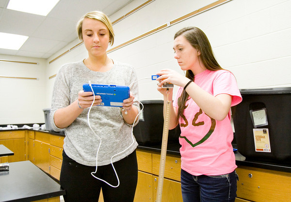 Seniors Anna Laura Nicholson, 18, left, and Ashleigh Dooley, 18, use an einstein Tablet+ with a force meter attachment during a lab on Isaac Newton's second law of motion in their integrated physics and chemistry class at New Albany High School on Thursday morning. New Albany is the first school in North America to use the new devices. Staff photo by Christopher Fryer