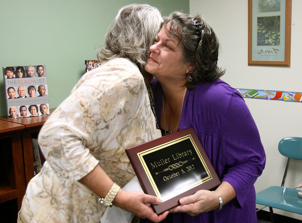 Corden Porter School teacher Diana Muller, right, hugs principal Bunny Nash-Gardner at the school's library dedication Friday. The library was named the Muller Library in honor of Ms. Muller who retired Friday after 27 years with Greater Clark County Schools. Staff photo C.E. Branham
