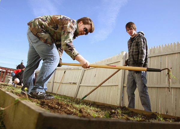 Rock Creek Community Academy seniors Steven Richey, left, and Michael Stearns weed a garden plot at the Clark County Youth Shelter Friday morning. Students from the Sellersburg school spent about five hours volunteering at the shelter. Staff photo by C.E. Branham