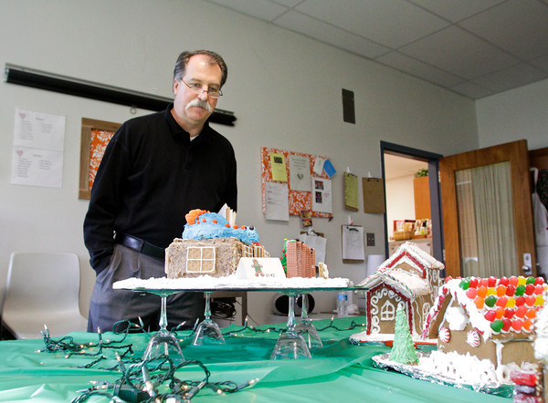 Silver Creek High School teacher Fred Finch looks over gingerbread houses while judging them for the advance foods class gingerbread house contest at the school on Wednesday afternoon in Sellersburg. This is the ninth year for the competition where seniors, in teams of four, are given raw materials to bake and construct gingerbread structures and scenes. Staff photo by Christopher Fryer