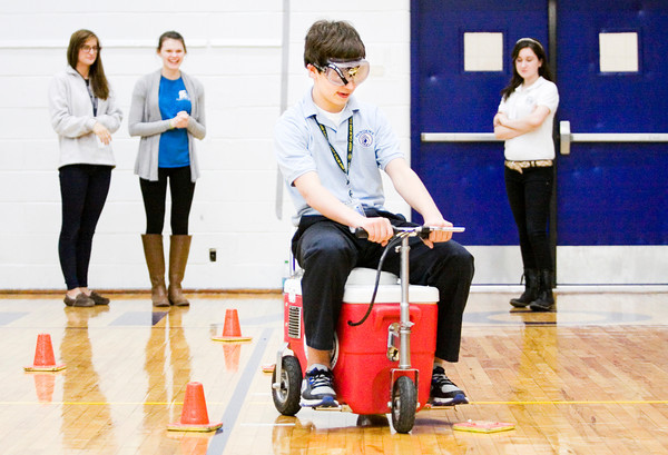 Freshman Lucas Murphy, 15, New Albany, operates a motorized cooler while wearing drunk goggles during an event facilitated by Indiana Students Against Destructive Decisions at Providence High School in Clarksville on Monday afternoon. Staff photo by Christopher Fryer