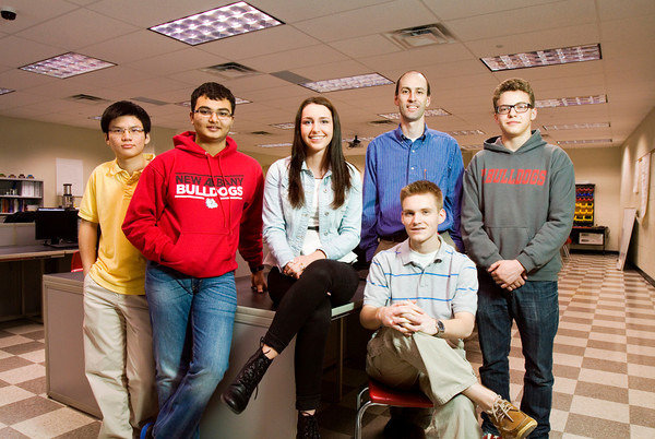 From left, juniors Kent Vuong, Kunal Bhanushali, and Franci Burton, teacher sponsor Martin Wright, and juniors Ben Fouts, seated, and Luke Rhoades stand in a lab at New Albany High School last week. The team, which also included junior Evan Scrivner, not pictured, developed an idea for an application for the Verizon Innovative APP Challenge that calculates the most efficient route between different locations to reduce pollution by increasing fuel efficiency. They placed first in Indiana on the high school level. Staff photo by Christopher Fryer