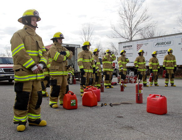 Fire rescue students look on as fellow students clean up after portable fire extinguisher training on a chemical fire at Prosser Career Education Center in New Albany on Thursday morning. Staff photo by Christopher Fryer