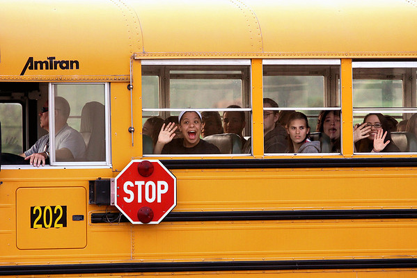 Henryville students wave to a crowd gathered to greet them on their first day of classes at Mid-America Science Park in Scottsburg, Ind., on Monday, April 2. Staff photo by C.E. Branham