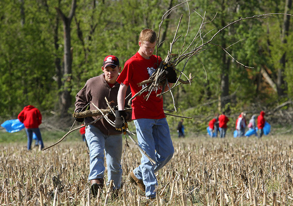 New Albany High School Navy JROTC cadets Tre Lynch and James Hoffman carry piles of debris off a 17 acre corn field in Pekin on Wednesday morning. Cadets form the New Albany and Floyd Central NJROTC programs cleaned two large parcels to help farmers get ready to plant. Staff photo by C.E. Branham