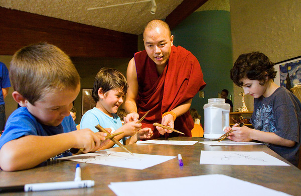 Buddhist monk Tenpa Phuntsok helps students make sand sculptures during a visit to Community Montessori in New Albany on Wednesday afternoon. He and three other monks from the Tashi Kyil Monastery in Dehra Dun, India, visited the school as part of their visit to the United States to help educate the public on Tibetan religion and culture. Staff photo by Christopher Fryer