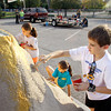 From left, St. Mary's Catholic Academy students Carolyn Kannapel, Savannah Meyer and Jack Chad work on an element for their school's Harvest Homecoming parade float on Wednesday afternoon in New Albany. The Harvest Homecoming parade will start at New Albany High School at noon on Saturday. Staff photo by Christopher Fryer