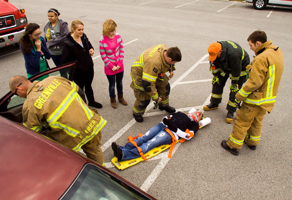 Greenville firefighters use Chassity Curtsinger, Sellersburg, to demonstrate the removal of a car wreck victim for Floyd Central students during the State Farm Celebrate My Drive event at the school on Wednesday afternoon. The event was held to educate 14 to 18-year-olds on dangerous driving behaviors as part of National Teen Driver Safety Week. Staff photo by Christopher Fryer