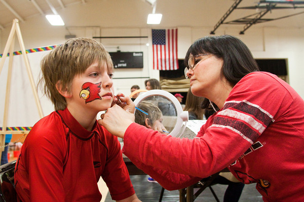 Parker Rappe, 10, of Henryville, has his face painted by Hsiao-Ling Gardner at a carnival booth during the Henryville Golden Band Spring Swing music program fundraiser at the high school on Saturday afternoon. Staff photo by Christopher Fryer