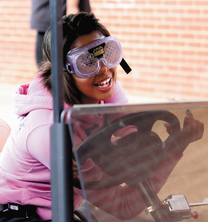 Tyrah Martin maneuvers a golf cart while wearing goggles that simulate driving at double the legal alcohol limit Thursday at Charlestown Middle School. Staff photo by C.E. Branham