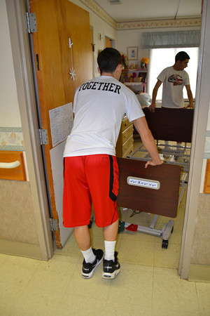 Mary Grzebieniak/NEWS<br /> Two New Castle High School athletes carefully roll a new bed into a patient room.