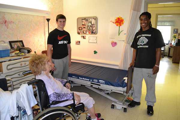 Mary Grzebieniak/NEWS<br /> Athletes James Humphrey (left) of New Castle High School and Will Graham of Slippery Rock University, deliver a new bed to a resident at Golden Hill Nursing Home Monday.