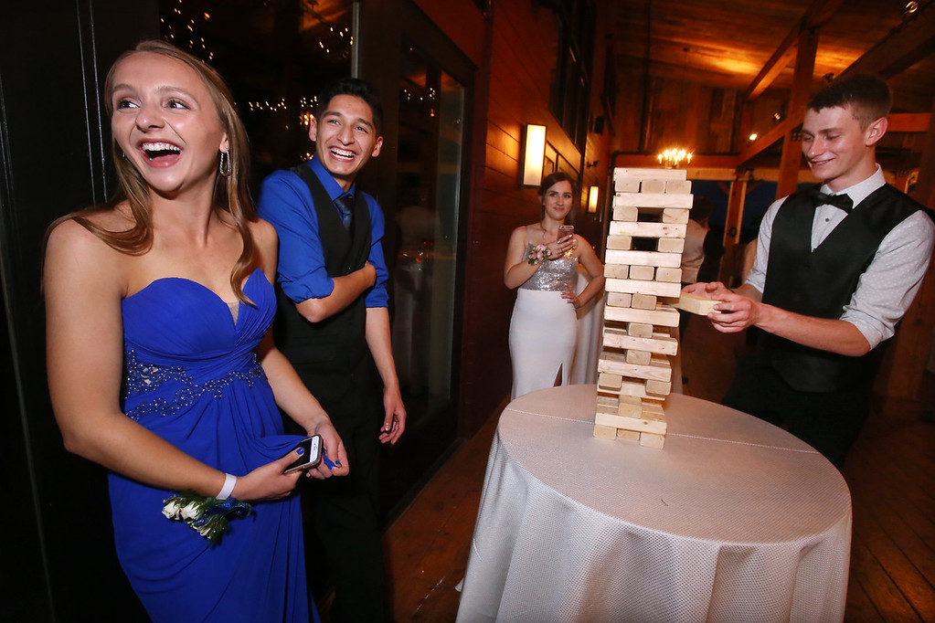 . From left, Molly Cadogan and Ulises Resendiz of Ayer, Tiana D\'Andrea of Lunenberg and Max Milkowski of Shirley, play Jenga at the Ayer-Shirley prom. (SUN/Julia Malakie)