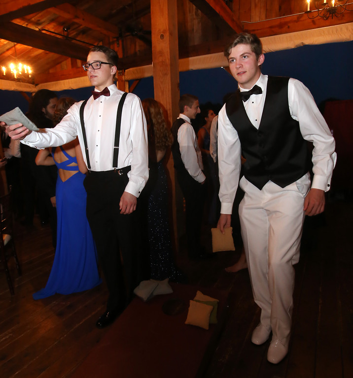 . Max Simmons, left, and Alex Patano, both of Ayer, play cornhole at the Ayer-Shirley prom. (SUN/Julia Malakie)