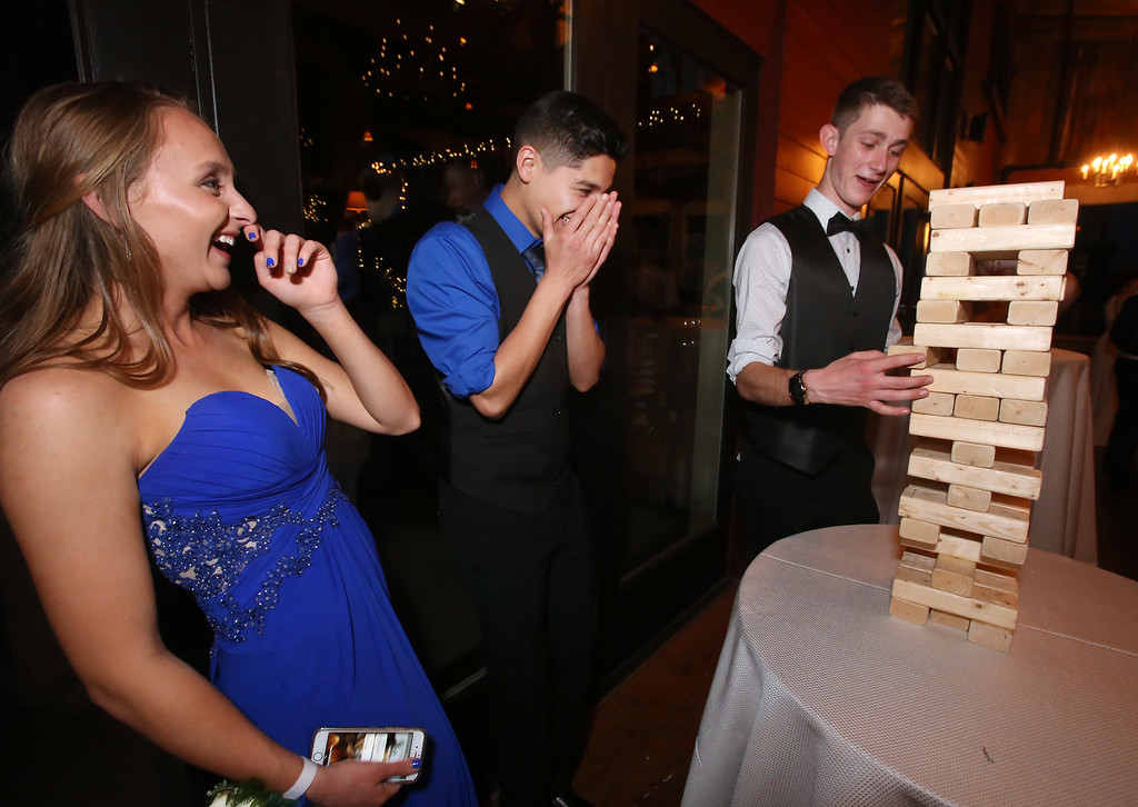 . From left, Molly Cadogan and Ulises Resendiz of Ayer, and Max Milkowski of Shirley, play Jenga at the Ayer-Shirley prom. (SUN/Julia Malakie)