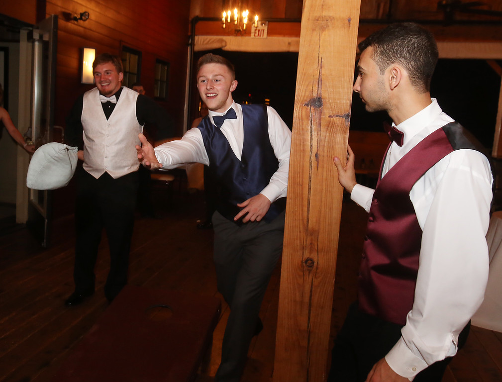 . From left, Ryan Martone of Ayer, Mick Mitrano of Shirley, and Gabriel Lauar of Ayer, play cornhole at the Ayer-Shirley prom. (SUN/Julia Malakie)