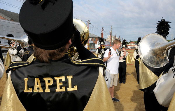 Don Knight    The Herald Bulletin<br /> Lapel band director Drew Steck squeezes in a little more practice with the Marching Bulldogs as they wait for the start of Band Day at the State Fair on Saturday.