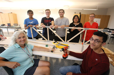 """Billerica High students competing for a InvenTeam Award get training on """"Design Thinking"""" from IBM employees. From left, Billerica High engineering teacher Amy Skrobis, rising sophomore Karan Rana, 14, and seniors James Pope, 17, and Jacob Isaac, 17, IBM senior solution architect Florence Lu of Billerica, and UX designer Erika Vargas of Townsend, and senior Vik Patel, 17, with one of their trusses. (SUN/Julia Malakie)"""