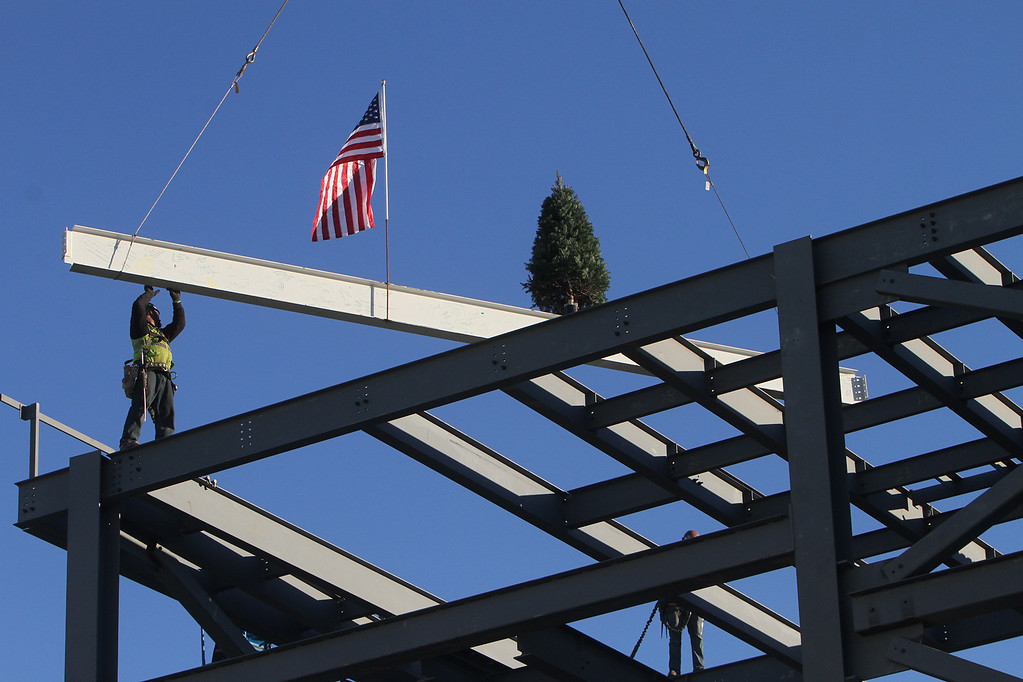 . Topping-off ceremony for the new Billerica Memorial High School.  Robert Yount of St. Johnsbury, VT, left, and Anthony Giordano of Gilbertville, Mass., rear, hidden, both with Stellar Steel Erectors, position the last beam. (SUN/Julia Malakie)