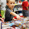 Holly Pelczynski - Bennington Banner 2nd grader, Mavrick Pratt picks out a book during the Monument Elementary school book fair on Wednesday morning..