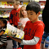 Holly Pelczynski - Bennington Banner Ryoya Ito, looks through a book during a book fair held at Monument elementary school in Bennington.