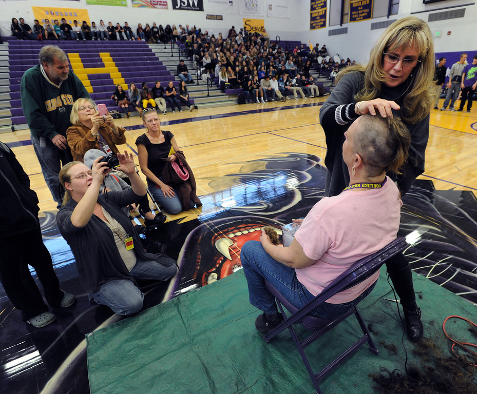 "Security staff member, Robbie Jerger, is having her head shaved for charity by Tamara Butler, while friends and family look on.<br /> Boulder High School held their Winter Rally on Thursday, with dance performances, team introductions, and head shaving for charity.<br /> For a video and more photos of the Rally, go to  <a href=""http://www.dailycamera.com"">http://www.dailycamera.com</a>.<br /> Cliff Grassmick  / January 10, 2013"