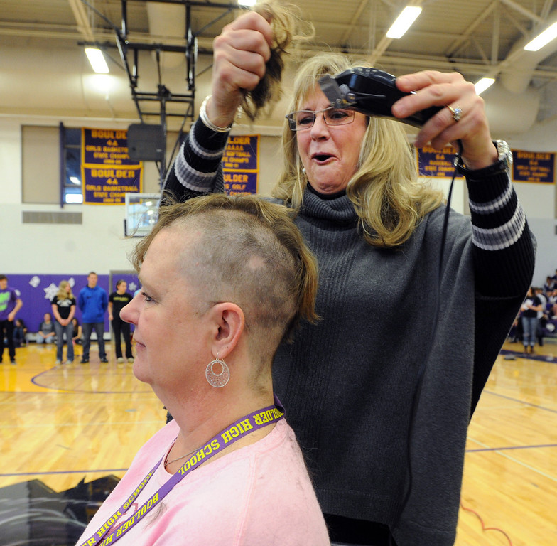 "Security staff member, Robbie Jerger, is having her head shaved for charity by Tamara Butler during the rally.<br /> Boulder High School held their Winter Rally on Thursday, with dance performances, team introductions, and head shaving for charity.<br /> For a video and more photos of the Rally, go to  <a href=""http://www.dailycamera.com"">http://www.dailycamera.com</a>.<br /> <br /> Cliff Grassmick  / January 10, 2013"