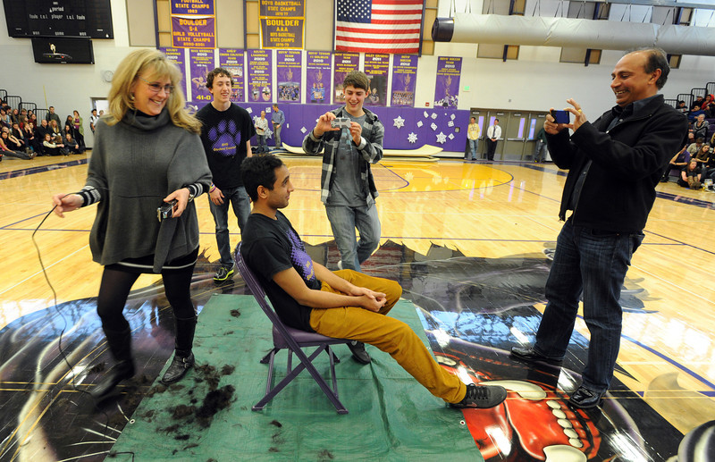 "Boulder High student, Neil Sandhu, is having his head shaved for charity by Tamara Butler during the rally. His father is documenting the event.<br /> Boulder High School held their Winter Rally on Thursday, with dance performances, team introductions, and head shaving for charity.<br /> For a video and more photos of the Rally, go to  <a href=""http://www.dailycamera.com"">http://www.dailycamera.com</a>.<br /> Cliff Grassmick  / January 10, 2013"