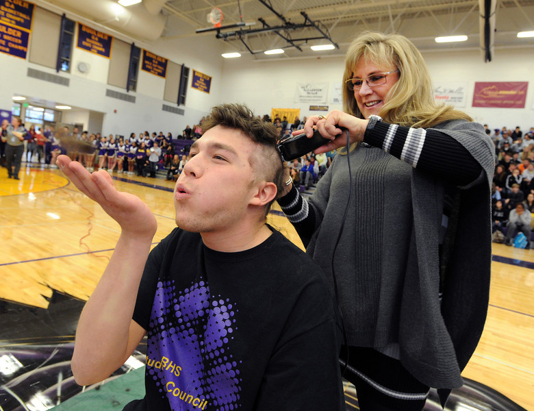 "Boulder High student, Ethan Rosen is having his head shaved for charity by Tamara Butler during the rally. Ethan is blowing the hair away.<br /> Boulder High School held their Winter Rally on Thursday, with dance performances, team introductions, and head shaving for charity.<br /> For a video and more photos of the Rally, go to  <a href=""http://www.dailycamera.com"">http://www.dailycamera.com</a>.<br /> Cliff Grassmick  / January 10, 2013"